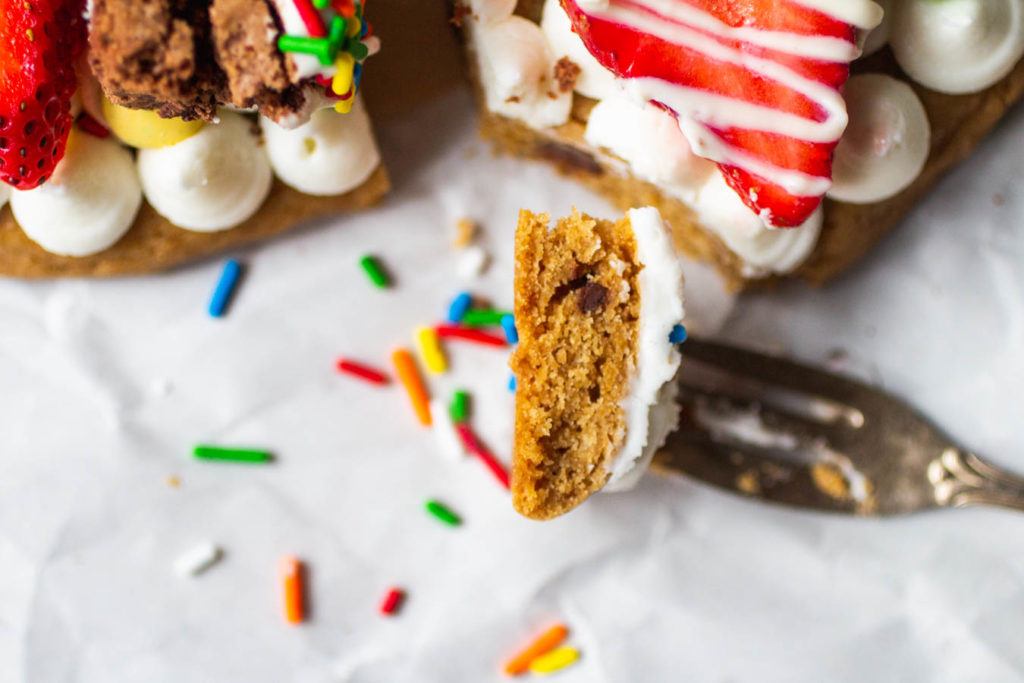 slice of birthday cookie cake with frosting and strawberry