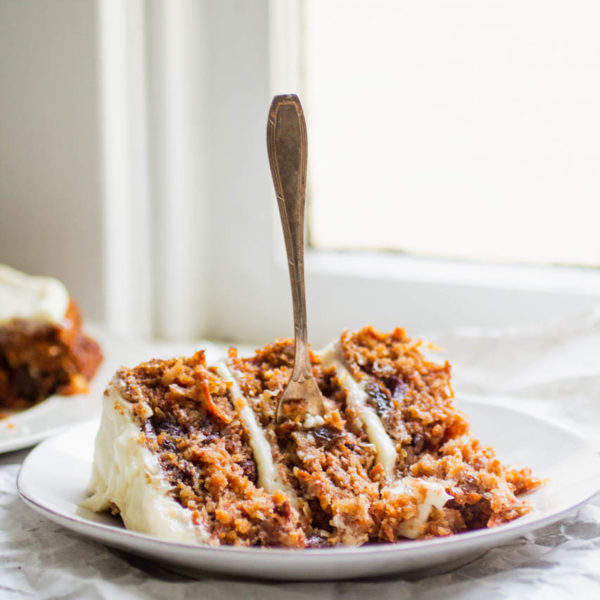 a slice of carrot cake with a fork on a white plate next to a window